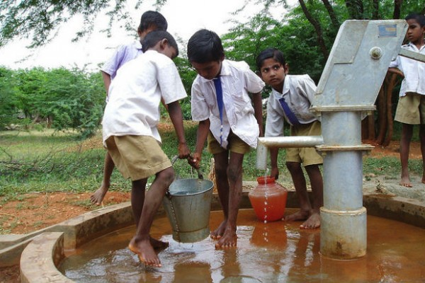 Schoolboys use handpump in midst of water crisis and World Water Day