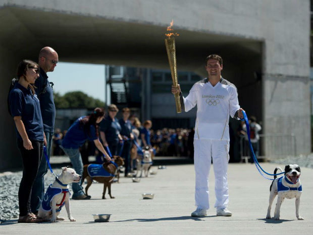 Former England soccer striker Michael Owen runs with Olympic torch through Battersea animal home
