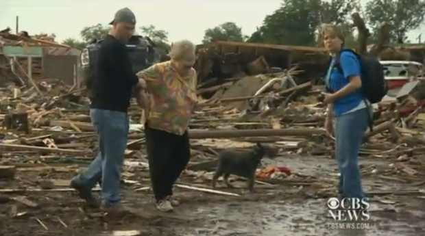An elderly tornado finds her dog trapped in rubble.