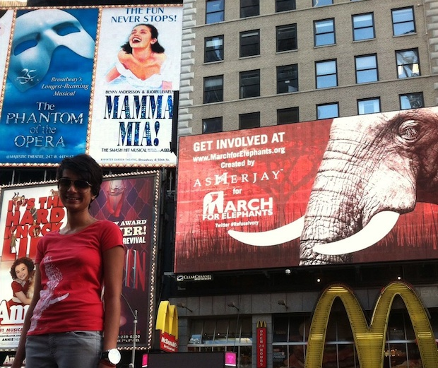 Asher Jay in front of the elephants in Times Square billboard